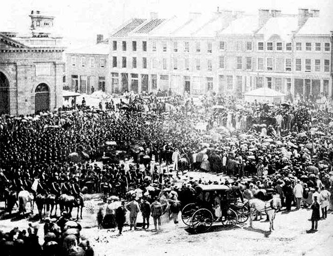 Period photograph of a crowd of people attending the proclamation of Confederation in Kingston's Market Square, 1867