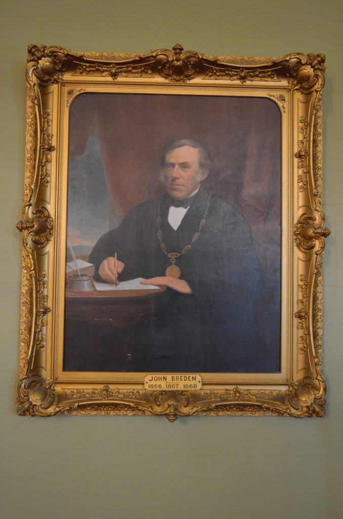Official portrait painting of Kingston's Mayor John Breden circa 1867, wearing his mayoral robe and chain, seated at his desk holding a pen and paper