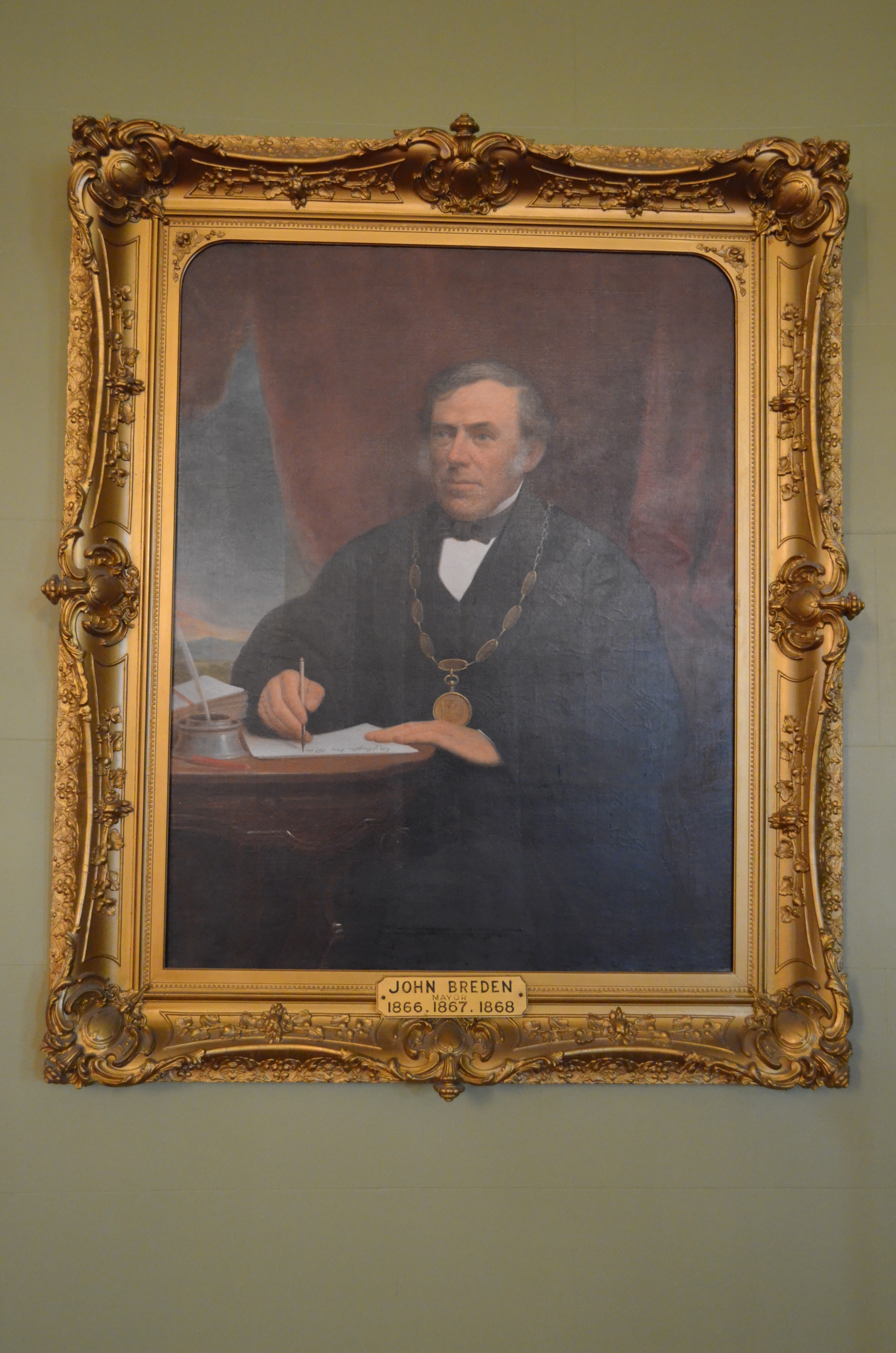 Portrait officiel de John Breden, maire de Kingston, assis à son bureau tenant une feuille et une plume.