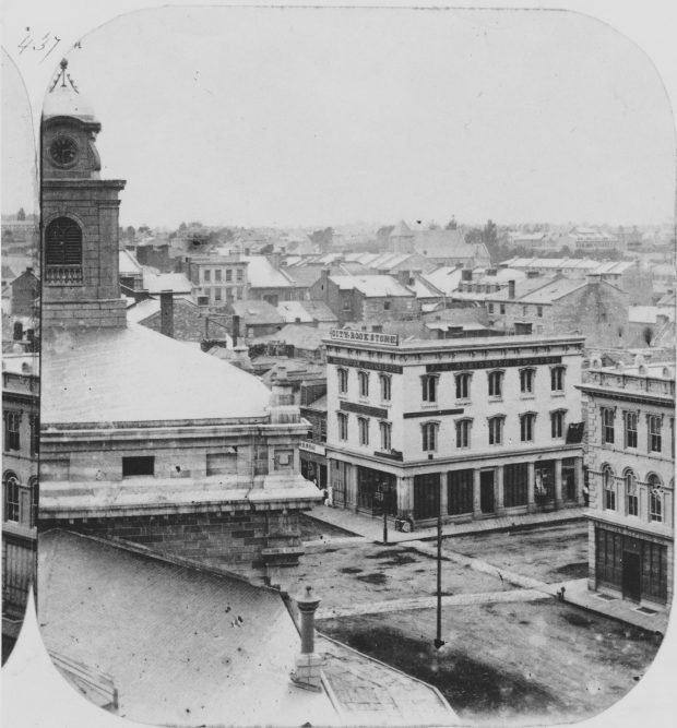 Streetscape photograph of Kingston in the 1860s with roads, sidewalks, and a number of buildings