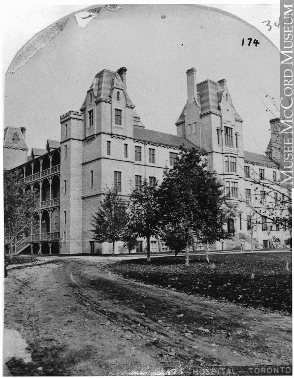 Photograph of Toronto General Hospital in 1868 with a roadway and trees in front of the building