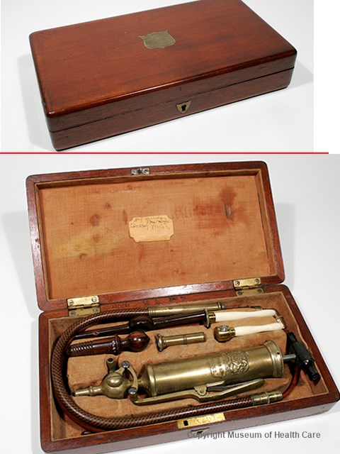 Photograph of a stomach and enema pump with metal syringe and tubing and accessories in a fabric-lined wooden case