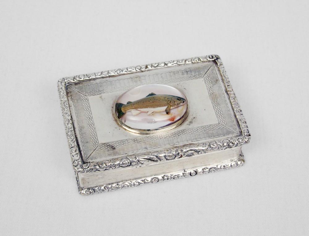 Boîte d'argent avec un intérieur d'or, sur le couvercle de la boîte on retrouve un médaillon de verre avec une effigie du saumon.