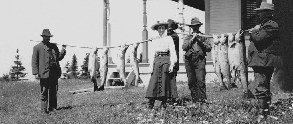 Silver print of Elsie Reford and her guides showing eight spectacular fish.