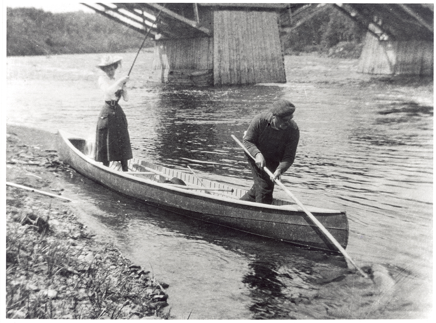Silver print showing Elsie Reford standing in a canoe at the river's edge. She is wearing a mid-length skirt, a white blouse, and a large elegant hat. She appears to be pulling on a large fishing pole. A man at the front of the canoe is lifting a large fish from the river with a long pole and hook.