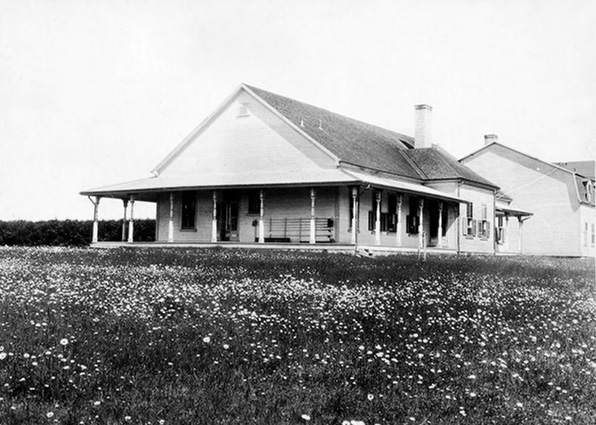 Silver print of the Estevan Lodge. You can see a Rod Rack to the right of the door and the centre of the building on the facade looking north to the field and the St. Lawrence River.