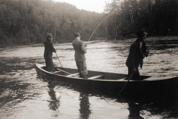 Lord Tweedsmuir fishing standing in a canoe on the Metis River