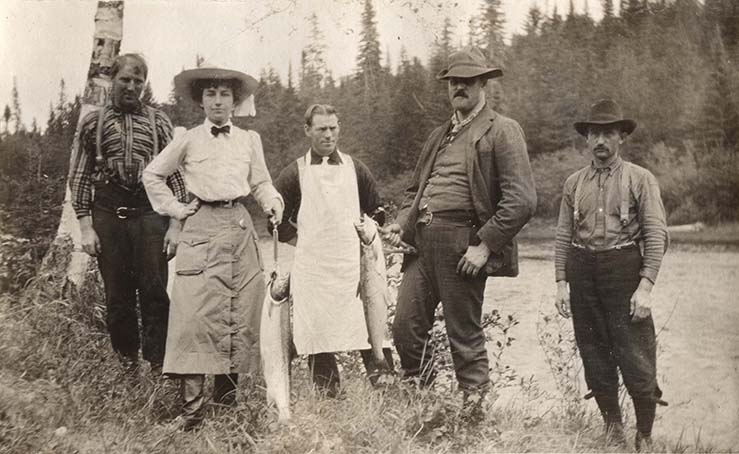 Silver print of Elsie Reford with four guides of the Tobique River showing two salmons.