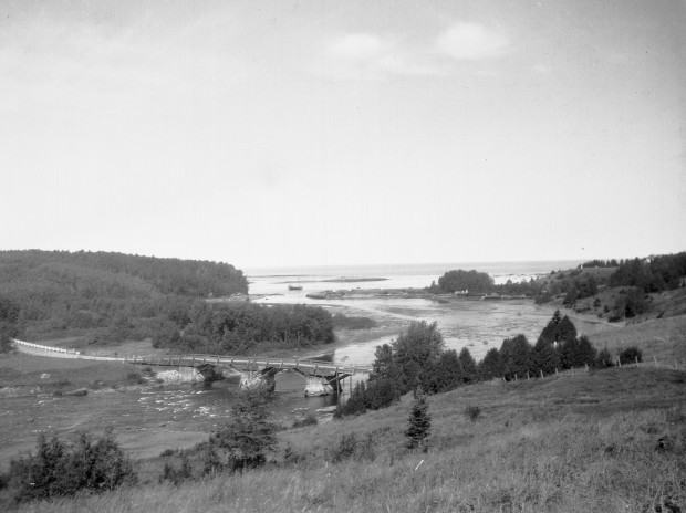View of the mouth of the Metis River showing the old wooden bridge, the remains of the wharf of the Price Brothers Company, a schooner and the mast at the belvedere of Estevan Lodge.