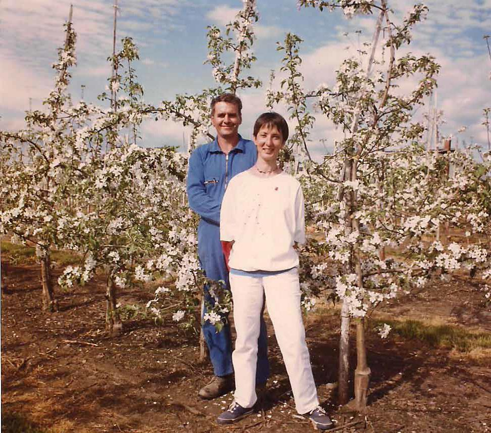 Colour photograph showing a woman and a man, Diane Goyette and Louis Poulin, standing in their orchard. The woman is dressed in white, the man in blue. Behind them, dwarf apple trees are visible.