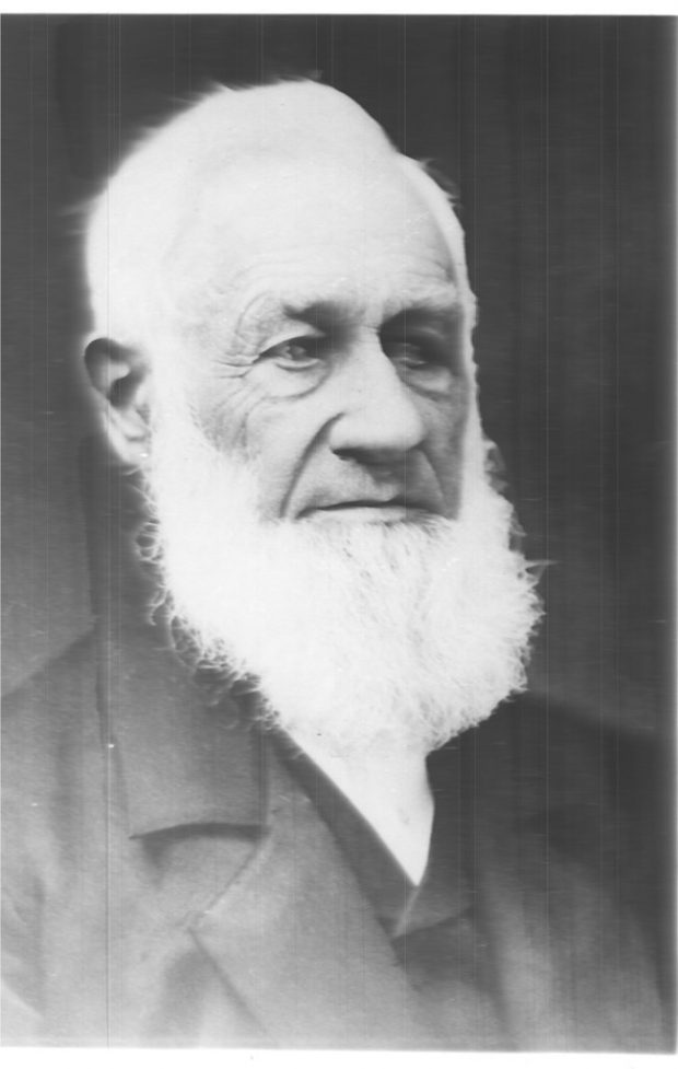 Black and white portrait photograph taken on an angle of Aaron Alexander Adams, with white hair and beard, dressed in a dark suit.