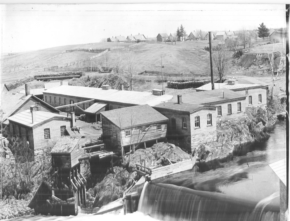 Black and white photograph of several factory buildings with falls from a dam on the Coaticook River in the foreground. In the distant background are some houses on the top of a hill.