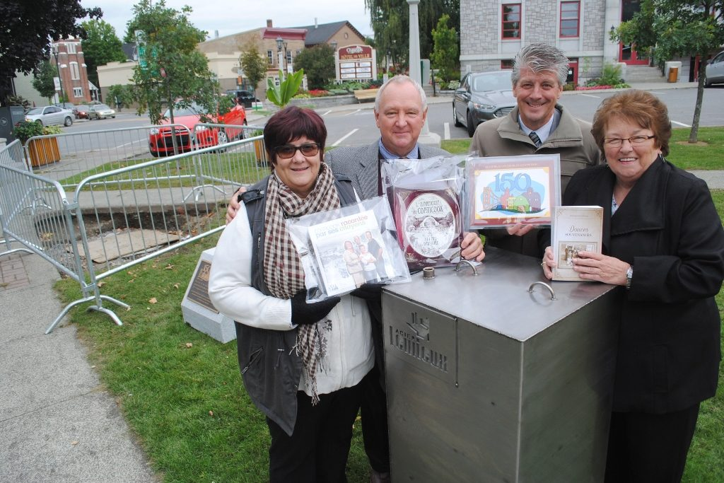 Colour photograph of four officials, two women and two men, posing beside the time capsule. They are holding documents produced for the 150th anniversary of Coaticook. Behind them is a partial view of downtown Coaticook.