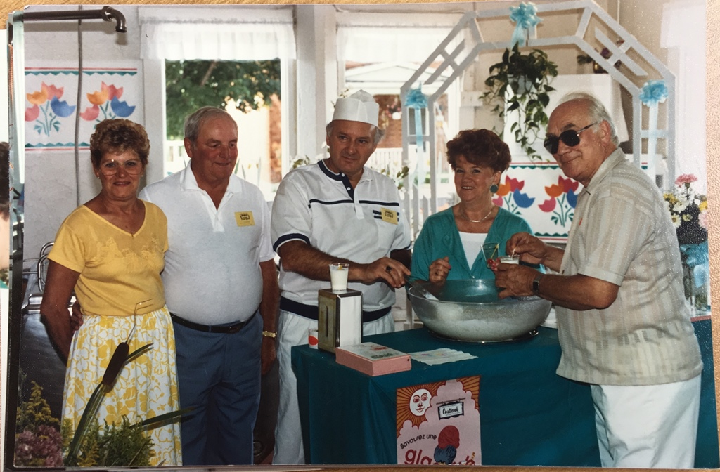 """Colour photograph of, from left to right, Thérèse Houle, Fernand Houle, Émile Provencher, Gisèle Provencher, and Archbishop Jean-Marie Fortier. The group stands around a table covered by a teal-coloured tablecloth, on which stands a transparent bowl filled with the """"Vison blanc"""" cocktail."""