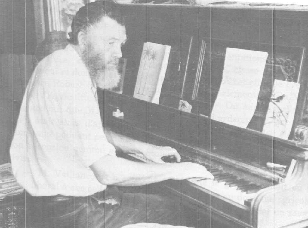 Photo noir et blanc de Dr Cecil Meade assis au piano. Des livres de partitions sont disposés sur le piano.