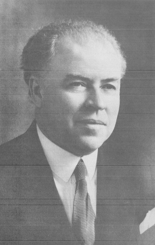 Black and white portrait photograph of Dr. Ernest Gendreau taken at an angle. He has grey hair and wears a dark suit, a white shirt and pocket square, and a white and grey tie.