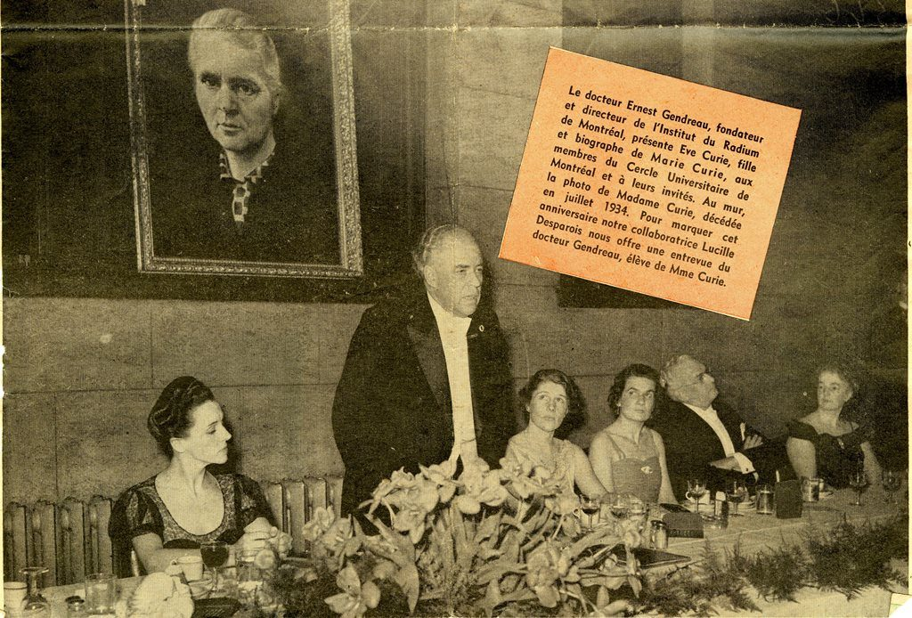 Black and white image of Dr. Ernest Gendreau wearing a black tuxedo with white shirt and bow tie, giving a speech at a reception in Montreal; four women and one man are seated at his table. Behind him a portrait of Marie Curie hangs on the wall. A clipping of text to the right explains the scene.