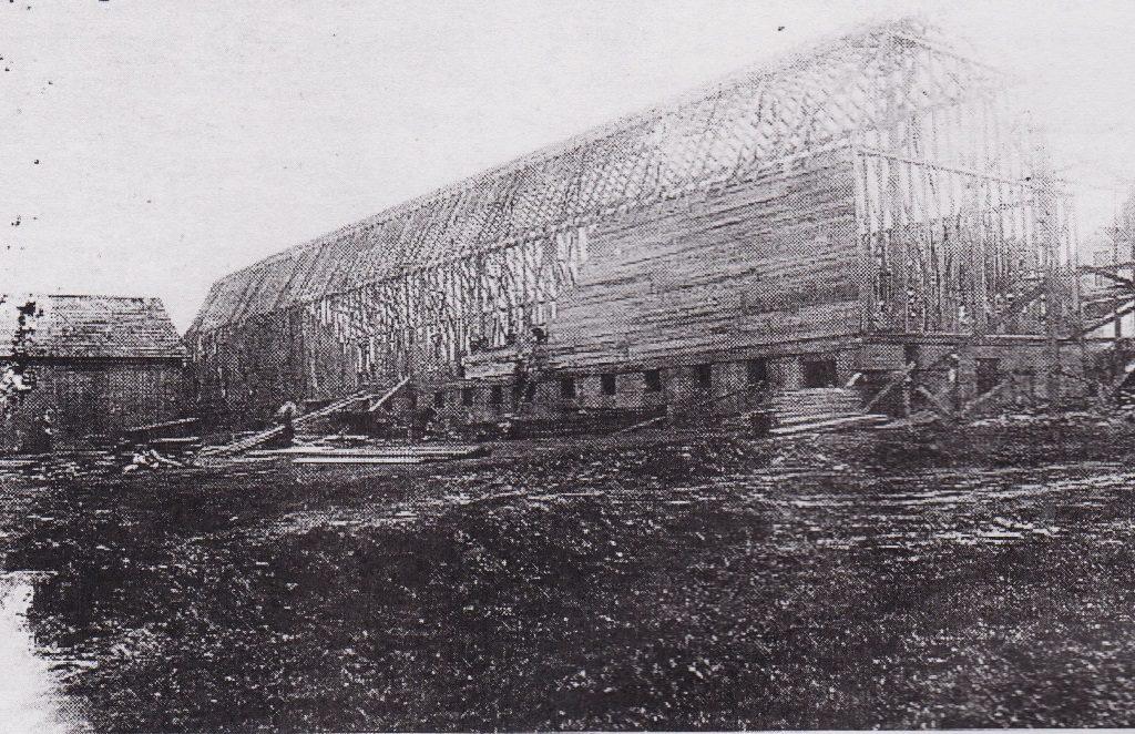 Photographie noir et blanc d'une énorme structure en construction dont la charpente est érigée. Des ouvriers commencent à la recouvrir de planches.