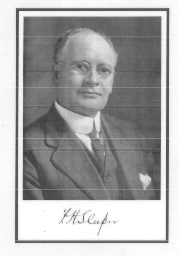Black and white portrait photograph taken at a slight angle of Frank Sleeper wearing glasses, a dark suit and tie, and a white shirt and pocket square.
