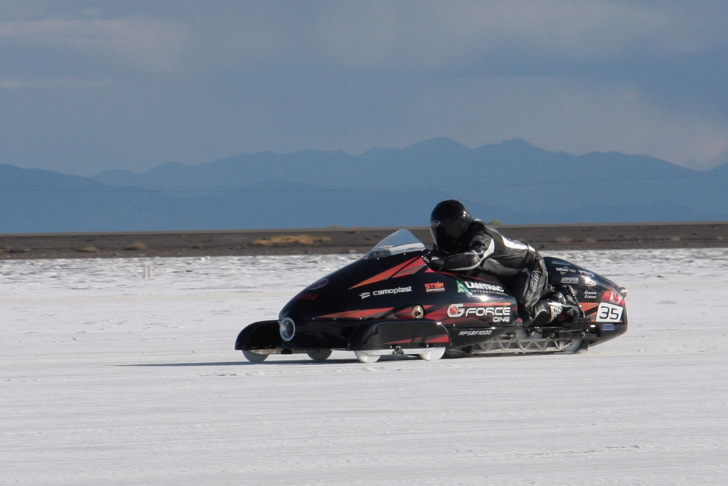 Colour photograph of a snowmobile being driven on a race course. The race is on the salt flats in the foreground; behind we see a stretch of desert land and a tall mountain range rises further back on the horizon.