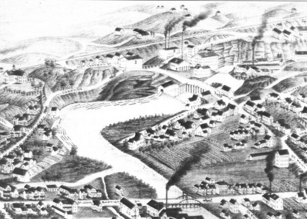 Black and white engraving of a map of a section of Coaticook. There are houses, buildings, roads, and a viaduct, with open fields at the top of the engraving.