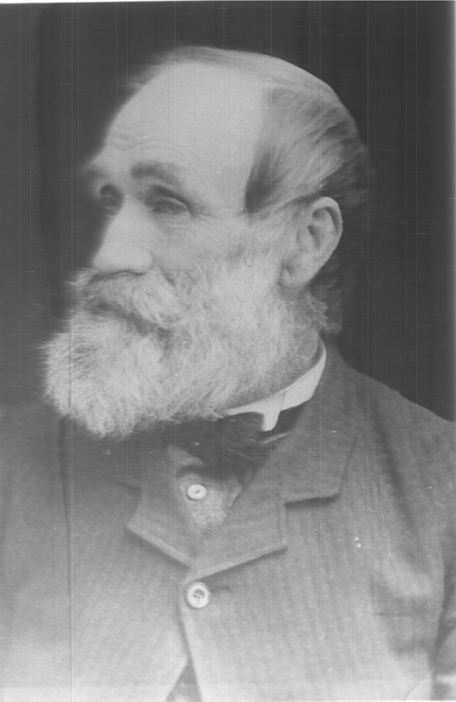 Black and white portrait photograph of Samuel Cleveland facing to the side; he has a white beard and mustache, and is dressed in a grey striped suit with a black bow tie.