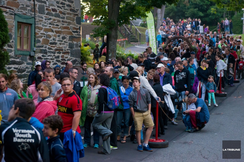 Colour photo of people standing in a long line to see Foresta Lumina, waiting in front of an old brick building located at the entrance of the Coaticook Gorge park.