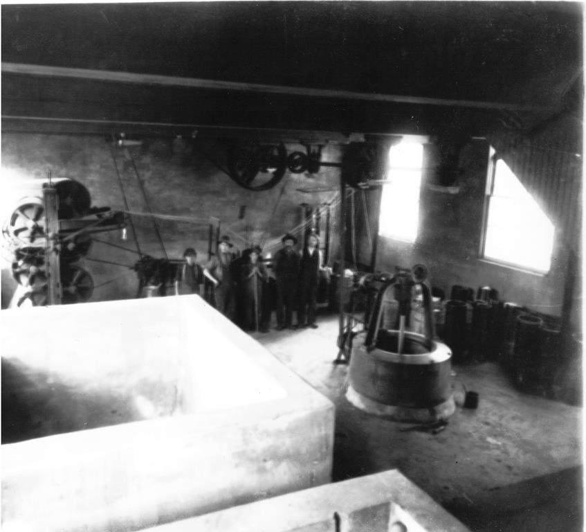 Black and white photograph of the interior of the factory, including machines, tools, materials and a few workers.