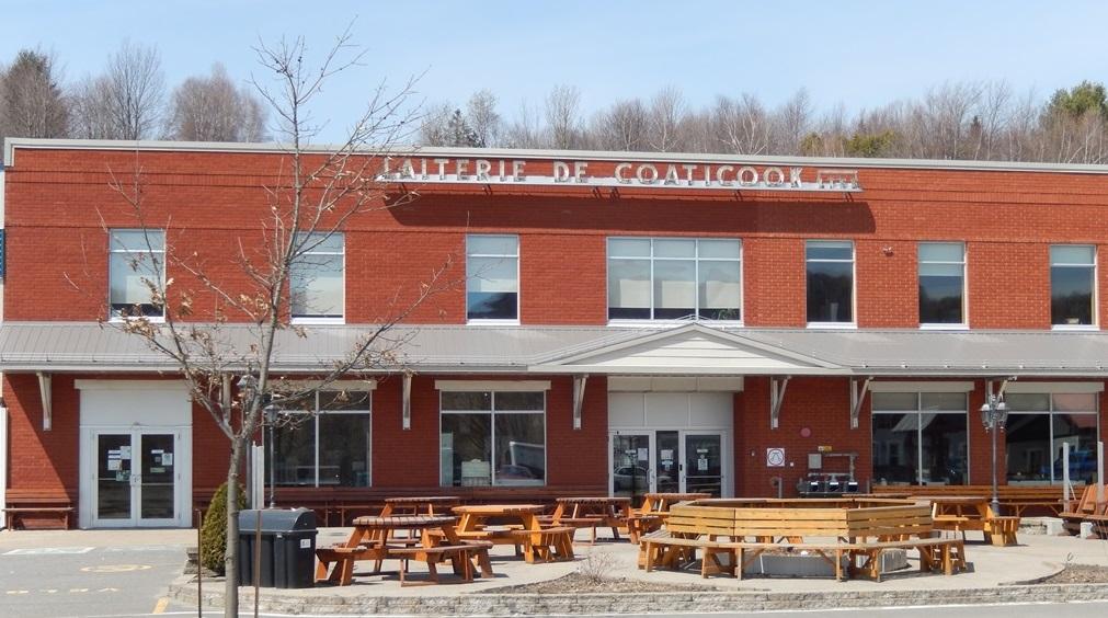 Photo couleur de la devanture d'un bâtiment de deux étages construit en partie avec des briques rouges. On peut voir les deux portes d'entrée, des fenêtres en vitres, des tables de pique-nique devant l'entrée principale.