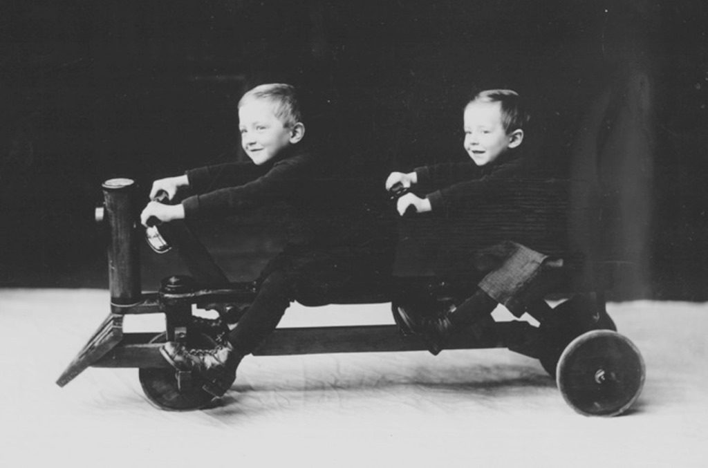 An old-fashioned black and white photograph of 2 smiling children seated on a cart that has 3 wheels and 2 sets of handlebars.