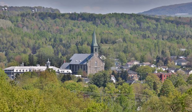 Colour photograph of a view of Coaticook surrounded by forested areas. The church and steeple of St-Edmond are visible, as well as the large building of the school Collège Rivier along with a few other buildings.