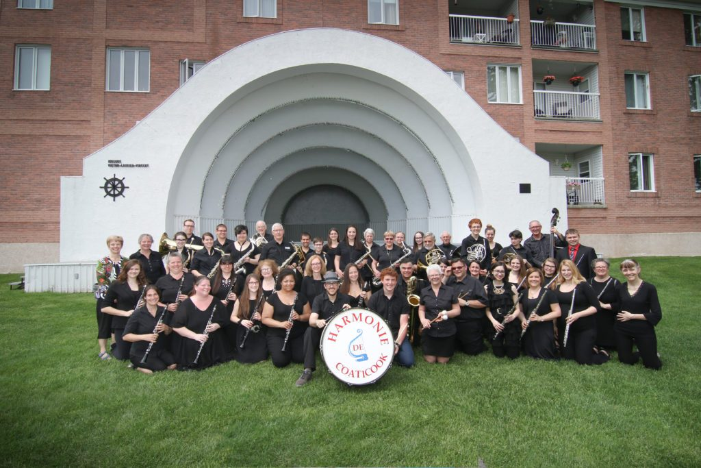 Colour photograph of a group of musicians from the Coaticook Harmony Band, all dressed in black except for the president, who wears a colourful outfit. They're standing in front of their outdoor concert stage, with a red brick apartment building in the background.