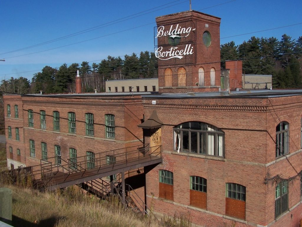 Colour photograph of the four-storey Belding Corticelli factory, built in red brick; a sign at the top of the building gives the name of the factory in stylized lettering. An iron walkway leads from the building to the road at left.