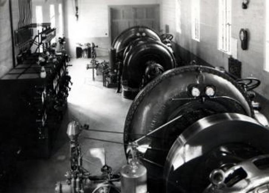 Black and white photograph showing machines and equipment in one section of the Coaticook Power Station.