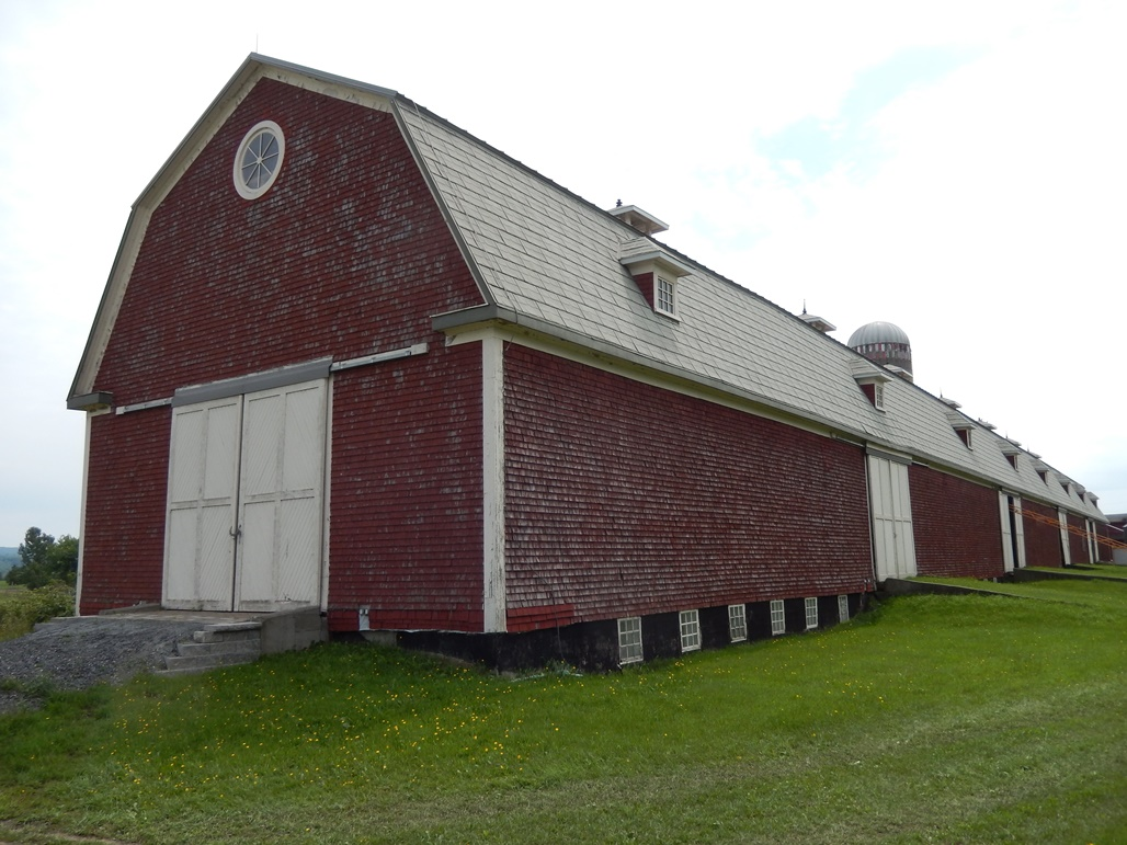 Colour photgraph showing the full length of the barn at Ferme-du-Plateau. The building is burgundy-coloured with white doors.