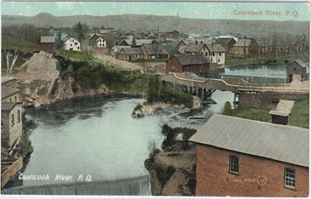 Historical colour photograph of an aerial view of the Coaticook River, showing a bridge and a few houses.