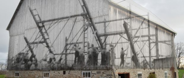 A contemporary photograph of a bank barn with a superimposed image of the work bee that raised it.