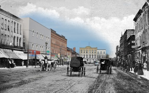A black and white photograph of horses and buggies superimposed on an image of a modern streetscape.