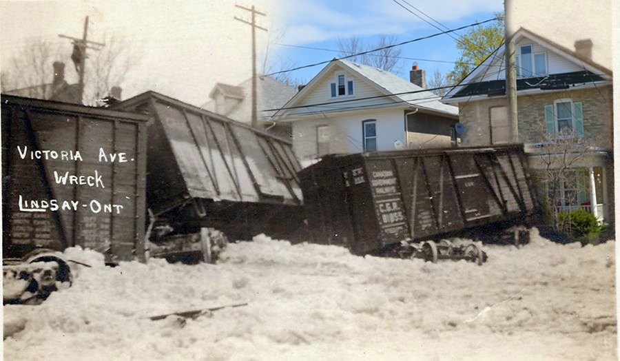 A black and white photograph of a train wreck superimposed on contemporary image of houses.