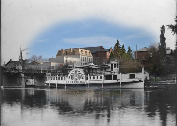 A black and white photograph of a steamboat superimposed on a contemporary image of a streetscape.
