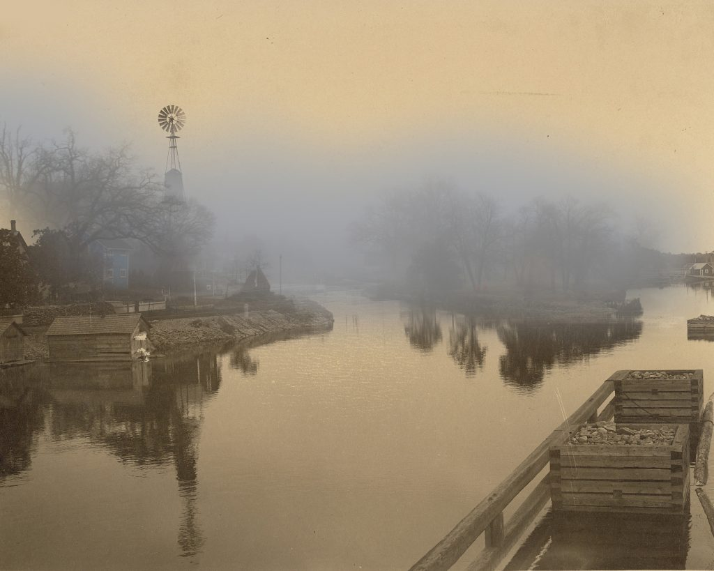 A B&W photo of a canal, with a blue carriage house visible through the mist.