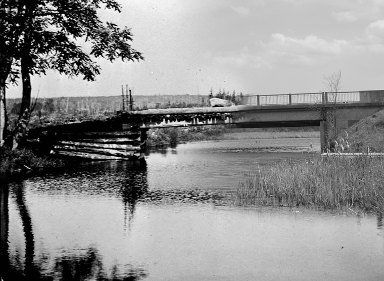 On the left a black and white photograph of a wooden bridge, on the right a contemporary image of a concrete bridge.