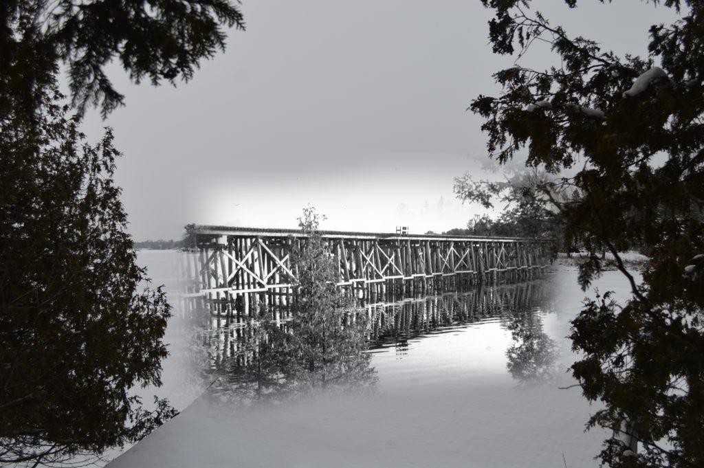 Une photo noir et blanc d' un pont à chevalets, superposée à une photo contemporaine d'un lac.