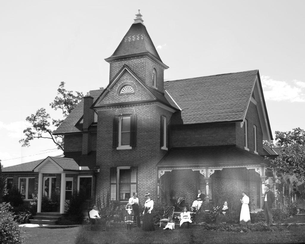Des photos noir et blanc fusionnées d'une maison en briques avec un une tour proéminente; la photo historique montre un groupe de personnes rassemblées sur la pelouse.