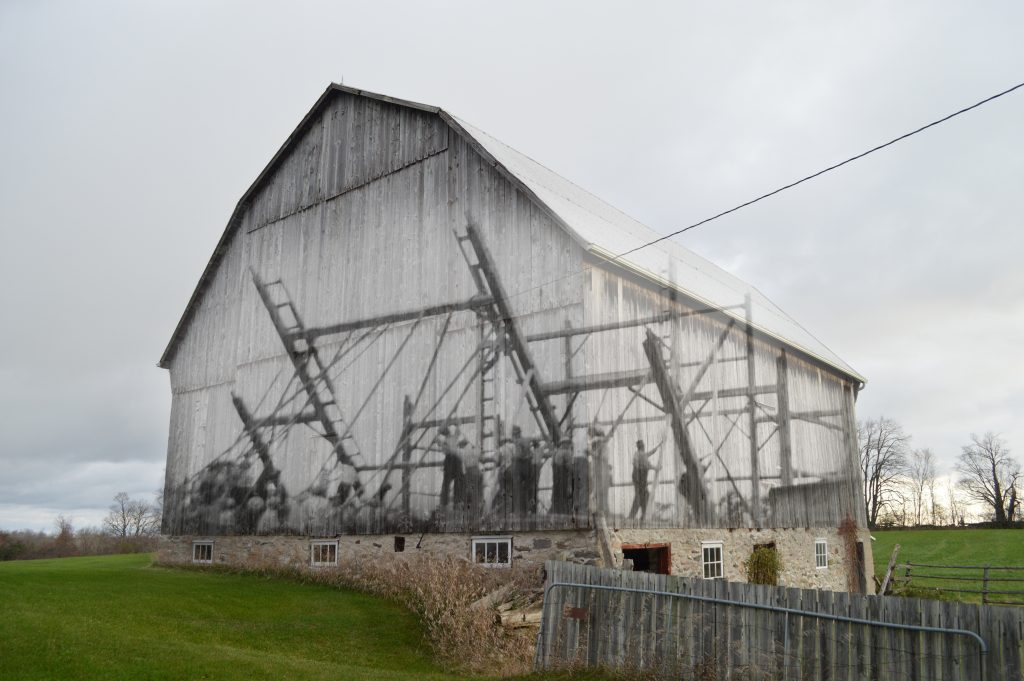 A contemporary photograph of a barn with a superimposed image of the work bee that raised it.