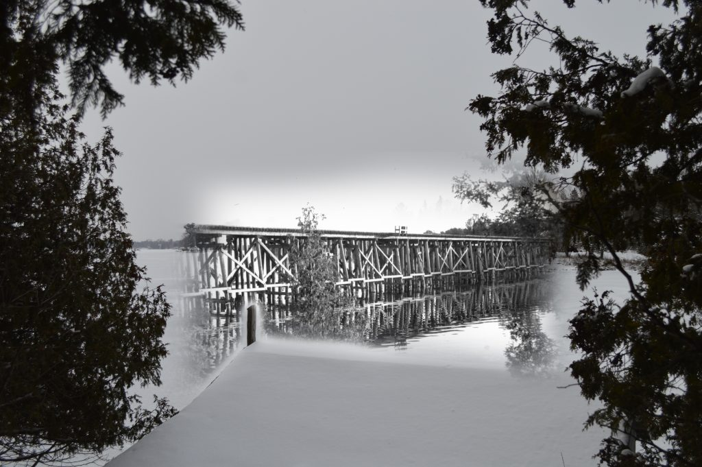 An image of a wooden railroad bridge fades into a contemporary image wherein the bridge is gone.