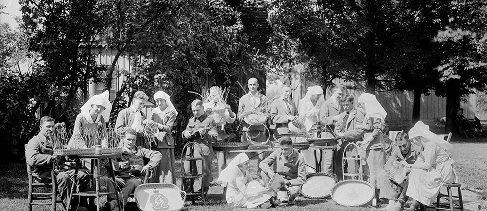 A black and white photo of several recovering First World War veterans with their nurses. They are outdoors on a bright day surrounding tables holding their crafted items.