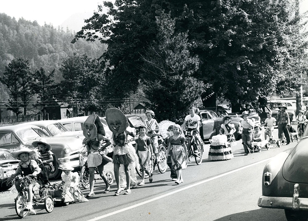 Black and white photograph of children in costumes, walking and riding bikes on a street as part of a parade, 1953.