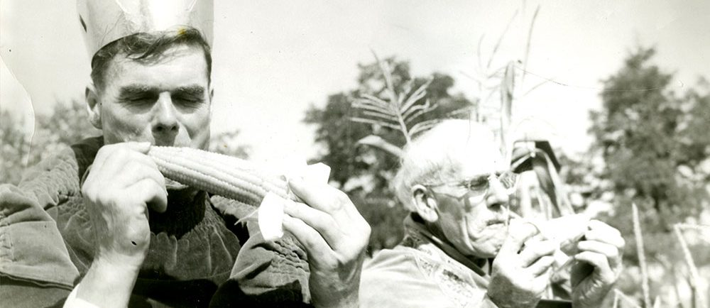 Black and white photograph of two men dressed in robes eating corn on the cob. The man on the left is 1950 Corn King Norman Morrow. The man on the right is 1949 Corn King Sam Stock.