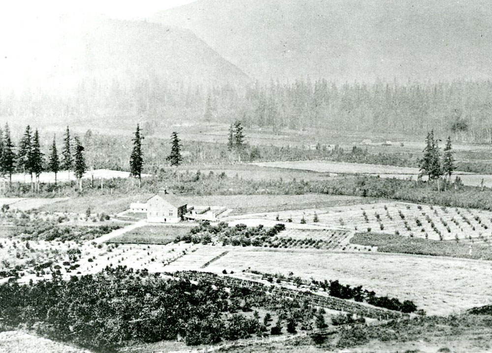 Black and white photograph of the Agassiz Dominion Experimental Farm. It is surrounded by fields, trees, and mountains.